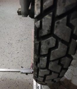 По кромке передней шины кладем выравниваем линейку